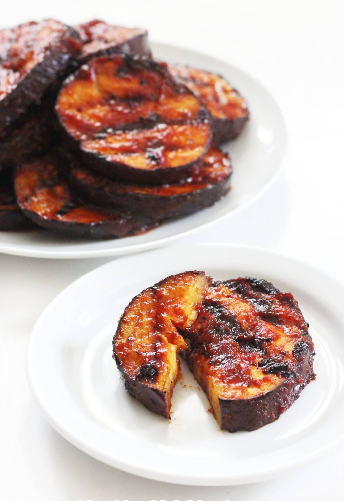 sliced grilled eggplant steak with bbq sauce on plate