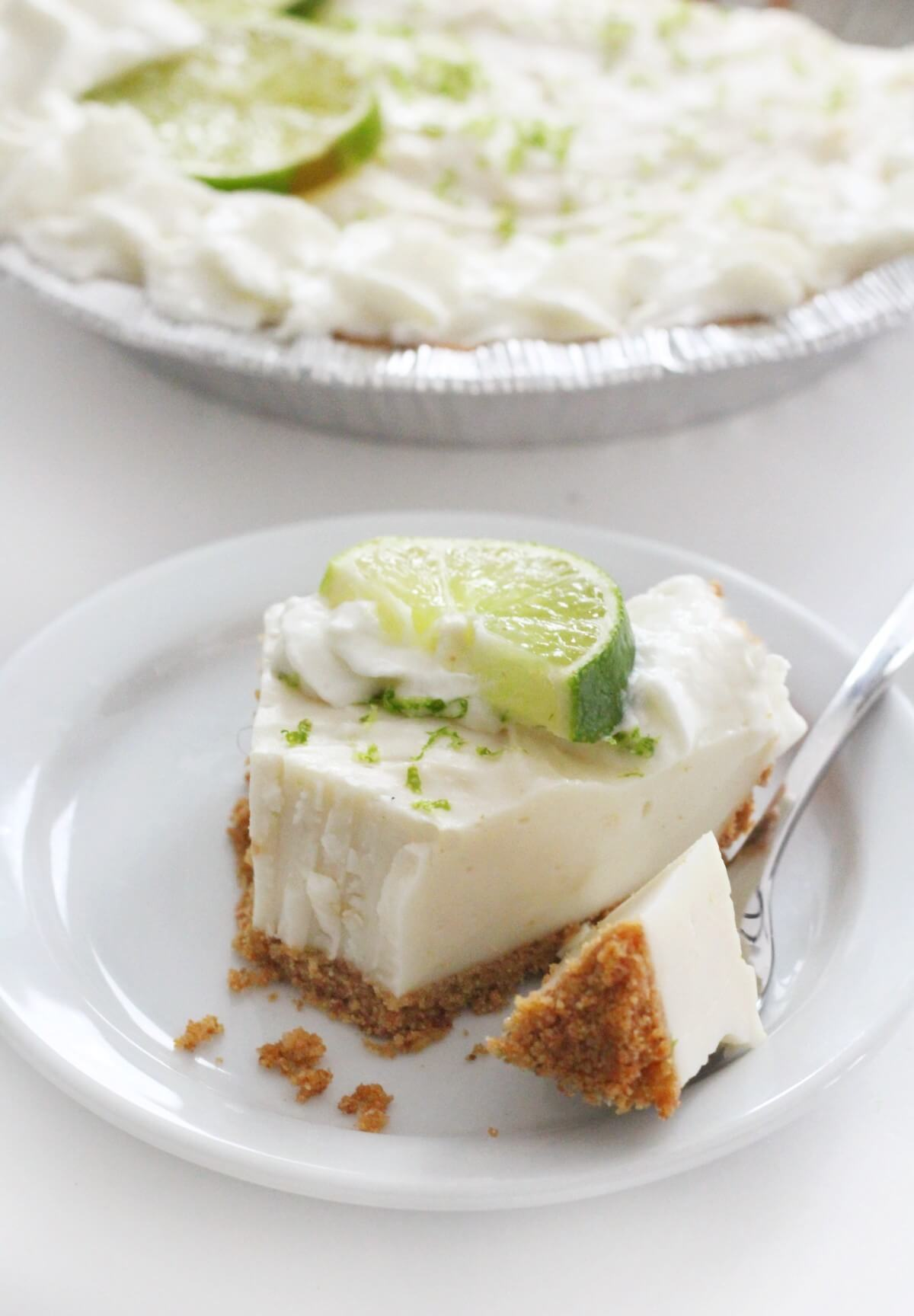 slice of vegan key lime pie and full pie in background