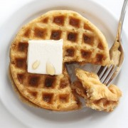 overhead view of crispy buttermilk waffles being eaten with syrup, butter, and fork
