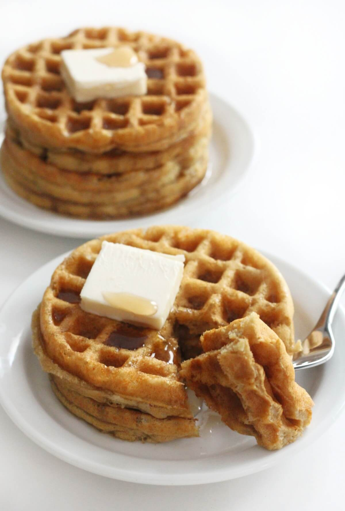 two plates of stacked gluten-free buttermilk waffles with syrup and vegan butter
