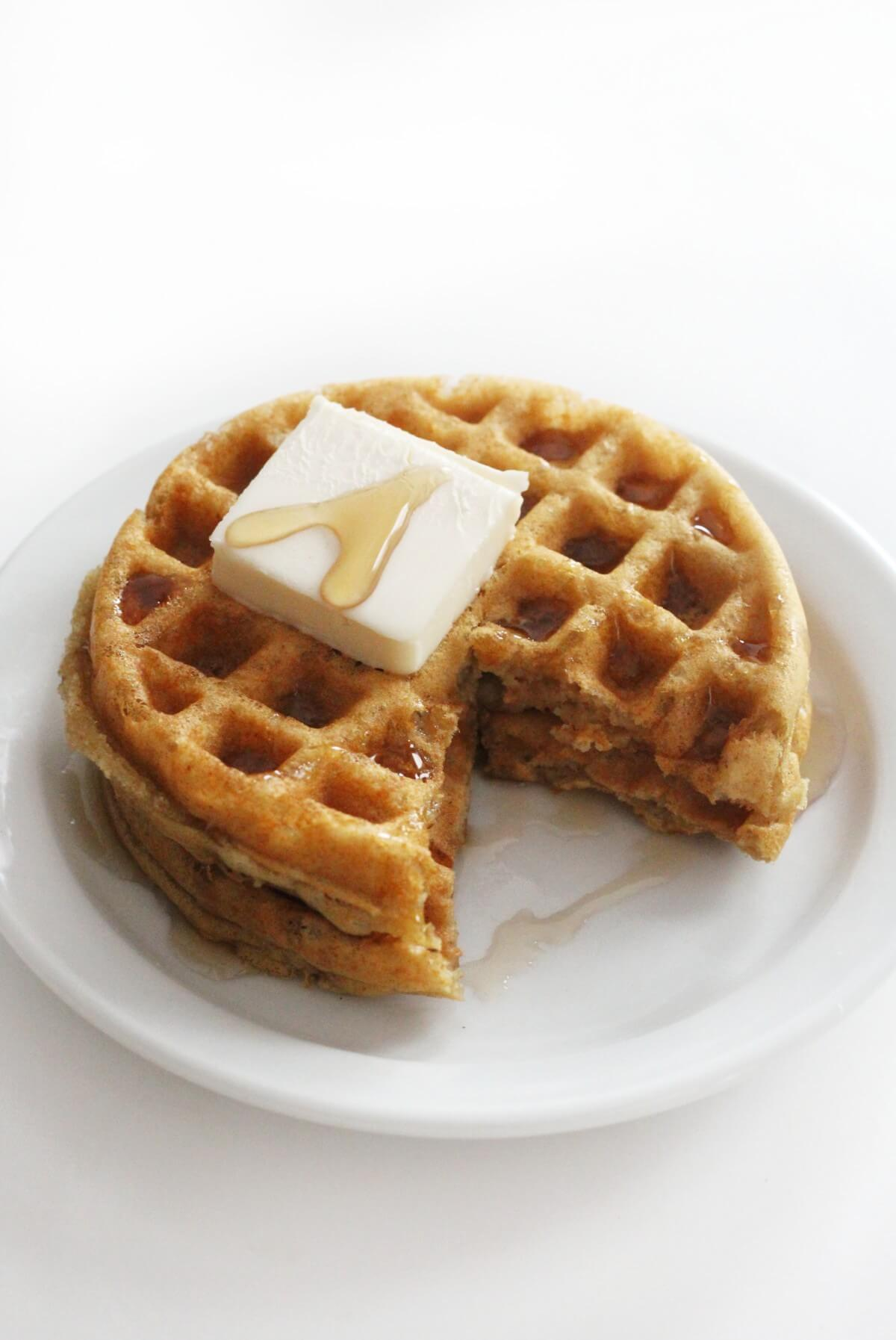 two stacked gluten-free buttermilk waffles with butter square and syrup