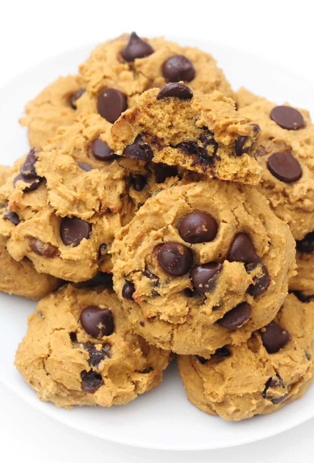 close up of bitten into vegan pumpkin chocolate chip cookie on pile