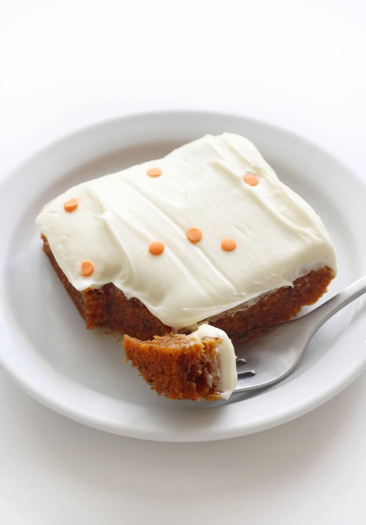slice of gluten-free pumpkin cake on plate with fork bite