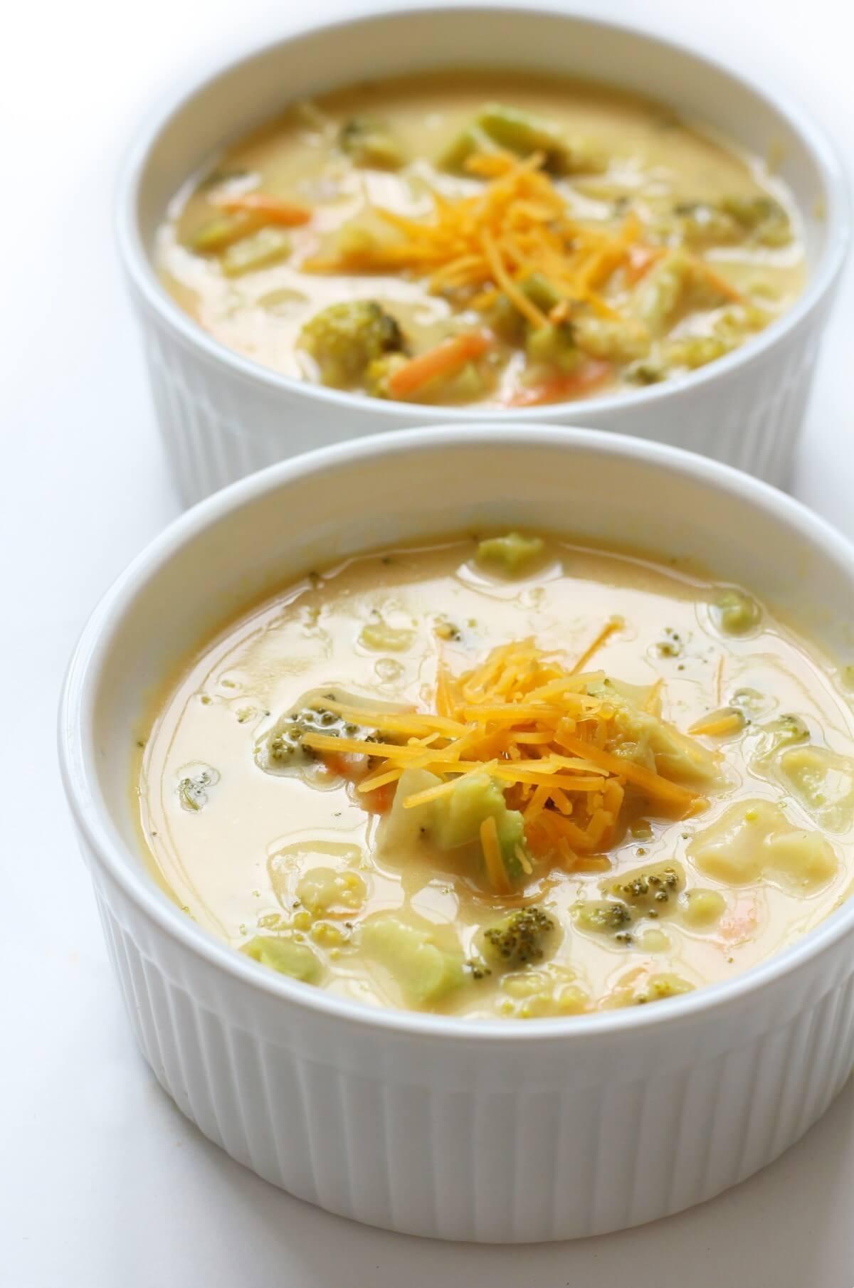 close up of two bowls of vegan copycat panera broccoli cheddar soup